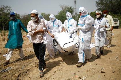 Familiares llevan el cuerpo de un hombre que murió por COVID-19, durante su funeral en un cementerio en Nueva Delhi, India (Reuters)