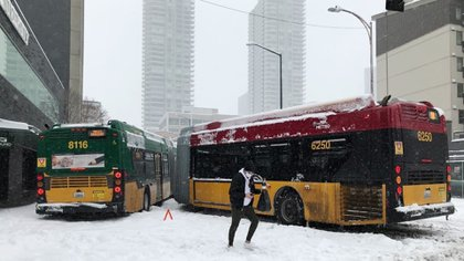 A pedestrian walks around two articulated buses jack-knifed at 3rd Ave and Battery St. in downtown Seattle on Saturday, Feb. 13, 2021. A winter storm has blanketed the Pacific Northwest with ice and snow, leaving hundreds of thousands of people without power and disrupting travel. (Fred Nelson/The Seattle Times via AP)