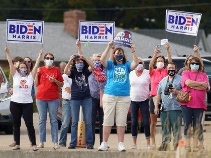 Un grupo de mujeres expresa su apoyo a Joe Biden mientras espera el arribo del candidato al aeropuerto de Erie, Pensilvania (Reuters)