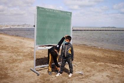 Dos estudiantes juegan al final de la clase en la playa (REUTERS/Nacho Doce)