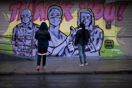 Dos mujeres frente a un mural del artista @Dister que muestra a los socorristas con máscaras y un mensaje de agradecimiento en el barrio de Harlem de Manhattan en la ciudad de Nueva York.
