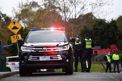 Agentes de la Policía de Victoria vigilan en las afueras de una torre de viviendas públicas en Racecourse Road en Melbourne, Australia, después de que se decretara el cierre inmediato de nueve torres en Flemington y North Melbourne tras registrarse un brote de coronavirus. EFE/EPA/ JAMES ROSS