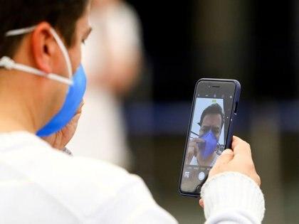 Foto de archivo: un hombre luciendo un barbijo se saca una foto con su teléfono celular en el Aeropuerto Internacional Ministro Pistarini de Buenos Aires, Argentina. 3 mar, 2020. REUTERS/Matias Baglietto