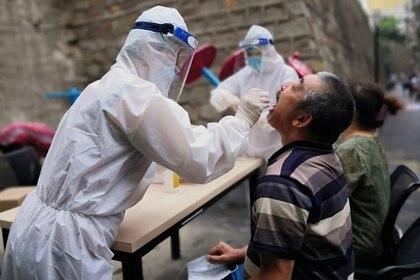 Un trabajador médico en traje de protección recoge un hisopo de un hombre para realizar pruebas de ácido nucleico gratuitas en Urumqi, provincia de Xinjiang, China, el 19 de julio de 2020. Fotografía tomada el 19 de julio de 2020. (Cnsphoto vía REUTERS)