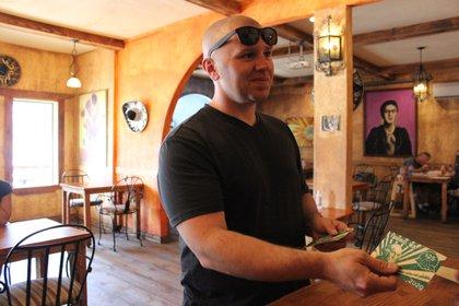 El alcalde paga en un restaurante usando la moneda local (Reuters)