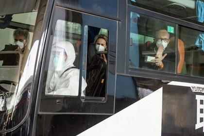 Miembros del equipo de la OMS encargados de investigar los orígenes de la pandemia de COVID-19 en un autobús mientras salen del aeropuerto internacional de Wuhan Tianhe en Wuhan, China, 14 enero 2021. (REUTERS/Thomas Peter)