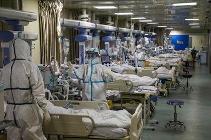 Médicos con trajes protectores atienden a pacientes de COVID-19 en la unidad de cuidados intensivos (UCI) de un hospital durante el brote de coronavirus en Wuhan. Los profesionales de la salud chinos fueron censurados y no pueden hablar sobre el brote en aquella ciudad por orden del régimen (Reuters)