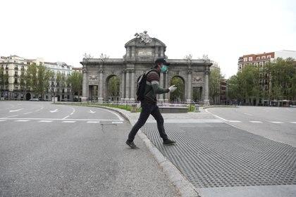 Un hombre con mascarilla camina por la Puerta de Alcalá, en Madrid (Reuters)