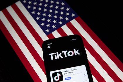 Un smartphone con la red social china TikTok junto a una bandera de Estados Unidos (EFE/Roman Pilipey)