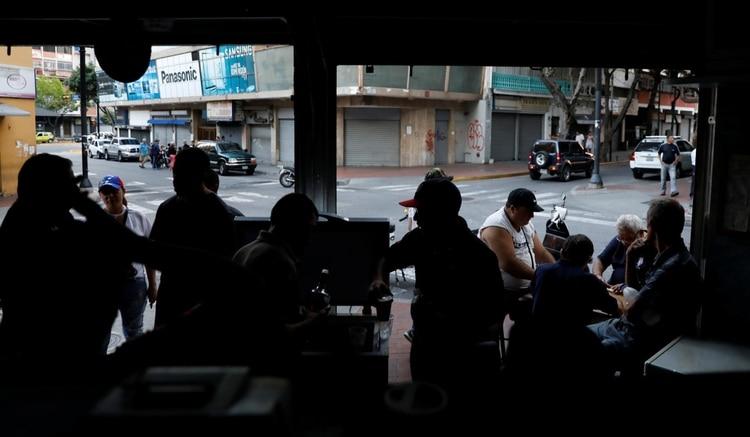 Un negocio intenta atender a oscuras durante un apagón (Reuters)