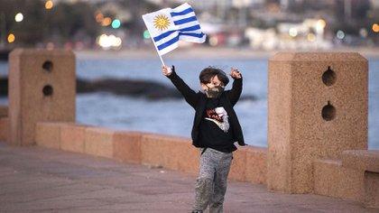Un niño con barbijo una bandera uruguaya en Montevideo (AP Photo/Matilde Campodonico)