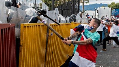 Los manifestantes intentaron romper el cordón policial arrojando piedras y agrediendo con palos a los uniformados (AFP)