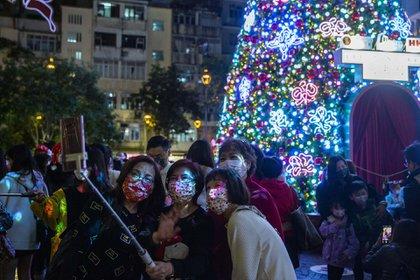 Un grupo de mujeres usando máscaras se toman una fotografía cerca de una pantalla en un centro comercial en Hong Kong. (Photo by ISAAC LAWRENCE / AFP)