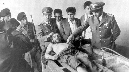 Un militar indica el disparo que acabó con la vida del Che Guevara. Su cadáver fue expuesto en la lavandería del hospital de Vallegrande, en Bolivia