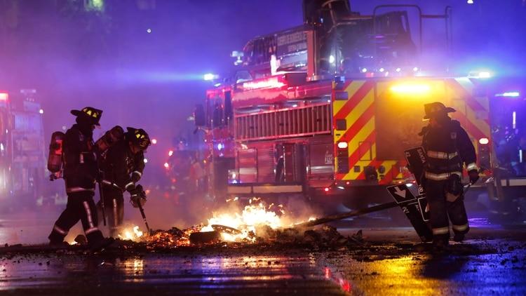 Bomberos intentan sofocar un incendio en el centro de Santiago. (AFP)