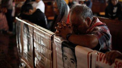 Familiares de los estudiantes desaparecidos rezan en la Basílica de Guadalupe, en Ciudad de México, junto a los carteles con sus imágenes mientras asisten a una misa para conmemorar el mes 63 desde la desaparición de los 43 jóvenes de la escuela Raúl Isidro Burgos en el estado Guerrero. 26 de diciembre de 2019. REUTERS/Henry Romero