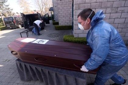 Un trabajador de la morgue con traje protector empuja un carrito con un ataúd de una persona que murió por la enfermedad del coronavirus (COVID-19), cerca de la ciudad de Charleroi, Bélgica [7 de abril de 2020] (Reuters/ Yves Herman)