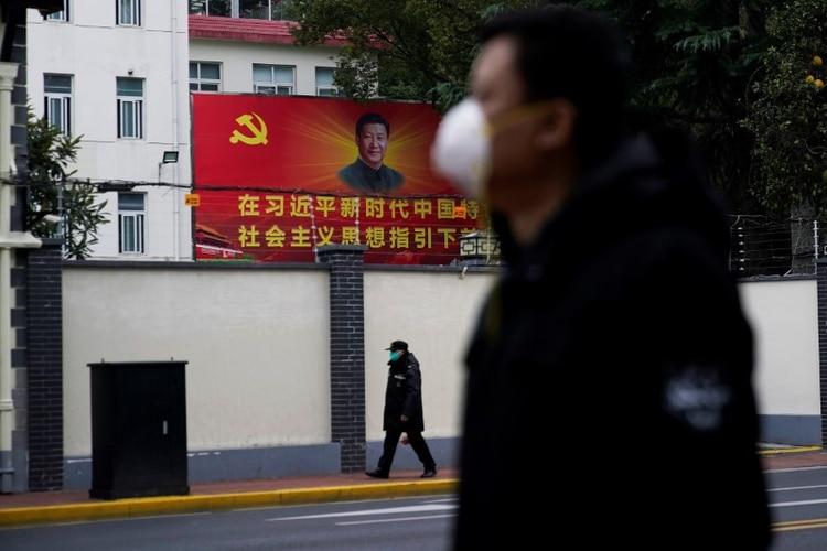 Foto de archivo de personas con mascarillas pasando por una calle junto a un retrato del presidente chino Xi Jinping mientras el país se ve afectado por un brote del nuevo coronavirus en Shanghai. 10 de febrero de 2020. REUTERS/Aly Song