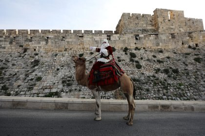 Issa Kassissieh wears a Santa Claus costume as he rides a camel after handing out Christmas trees to people during the annual distribution of the trees organised by the Jerusalem municipality, just outside Jerusalem's Old City December 22, 2020. REUTERS/Ammar Awad