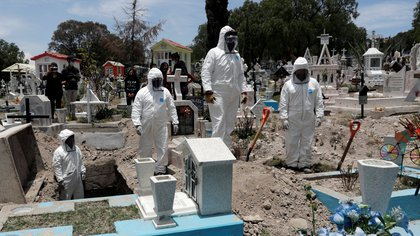 Cemetery workers wearing protective suits complete the burial of a man, who died of the coronavirus disease (COVID-19), at San Efren Municipal Cemetery, as the coronavirus disease (COVID-19) outbreak continues, in Ecatepec de Morelos, on the outskirts of Mexico City, Mexico June 19, 2020. REUTERS/Henry Romero