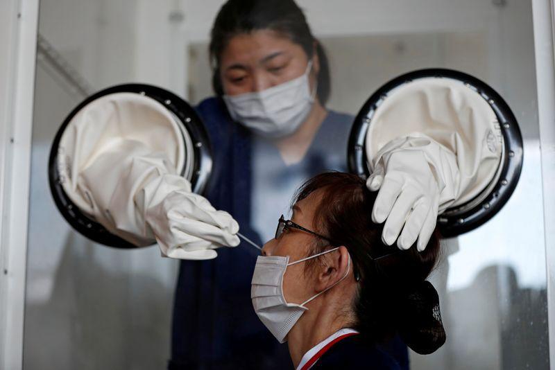FOTO DE ARCHIVO: Una trabajadora sanitaria realiza una prueba de test PCR para detectar la enfermedad COVID-19 en una instalación en Yokosuka, al sur de Tokio, Japón, el 23 de abril de 2020. REUTERS/Issei Kato