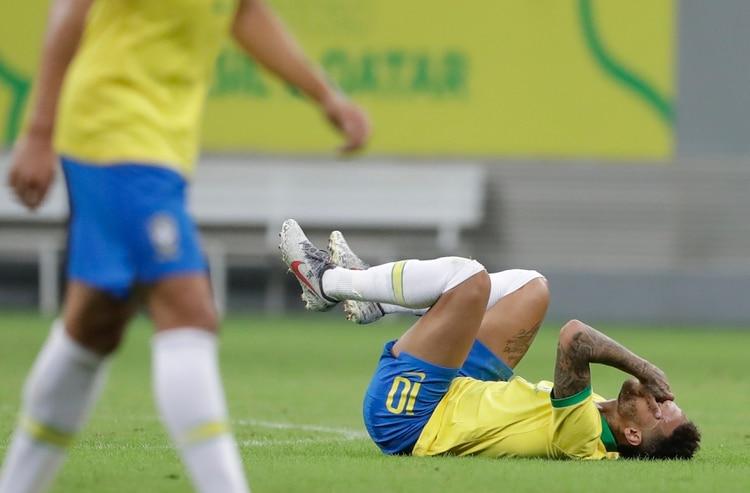 Neymar, de la selección de Brasil, se lamenta en la cancha tras recibir una falta durante un partido amistoso ante Qatar en Brasilia, el miércoles 5 de junio de 2019 (AP Foto/Andre Penner)