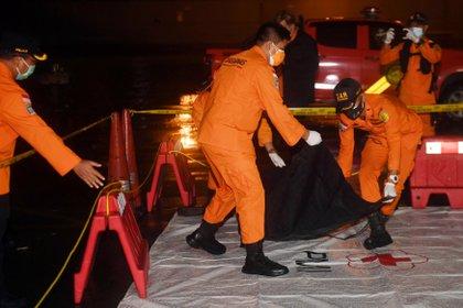 Miembros del equipo de rescate indonesio llevan una bolsa para cadáveres que presuntamente contiene restos del vuelo SJ182 del avión de Sriwijaya Air que se estrelló en el mar este 9 de enero de 2021 (Antara Foto/Akbar Nugroho Gumay/ vía REUTERS)