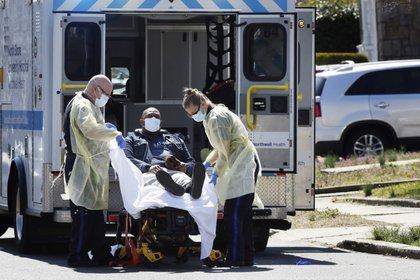 Técnicos de emergencias médicas llevan a un paciente con enfermedad por coronavirus (COVID-19) a una ambulancia mientras usan equipo de protección en la ciudad de Nueva York.