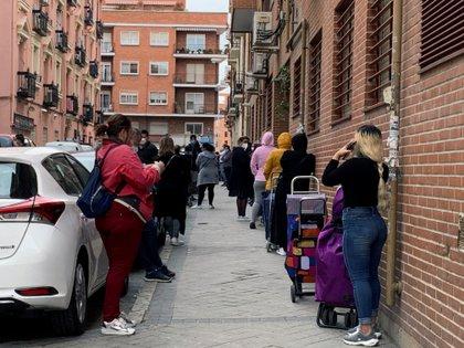 Vista de la fila de clientes que aguardan su turno para entrar al economato de Cáritas en el distrito madrileño de Tetuán. EFE/Rafael Cañas