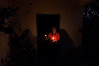 Una mujer ilumina fuera de su casa durante un apagón en la ciudad de Maracaibo (Venezuela). EFE/ Henry Chirinos /Archivo