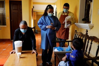 Una cuidadora (centro) conversa con un menor no acompañado que fue deportado desde Estados Unidos en un refugio en Ciudad de Guatemala. 31 de julio de  2020. REUTERS/Luis Echeverria