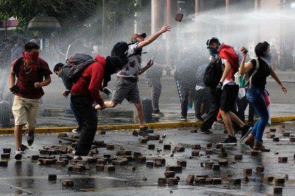 Manifestantes lanzan piedras durante una protesta contra el gobierno de Chile en Concepción, el 7 de noviembre de 2019 (REUTERS/Jose Luis Saavedra)