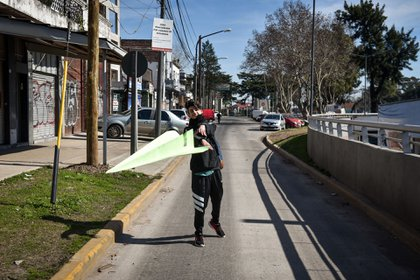 Un avión de papel y un adolescente en la calle de acceso al aeropuerto