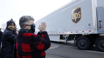 Vecinos de Michigan aplauden la salida de los camiones cargados de vacunas de la planta de Pfizer( AFP)