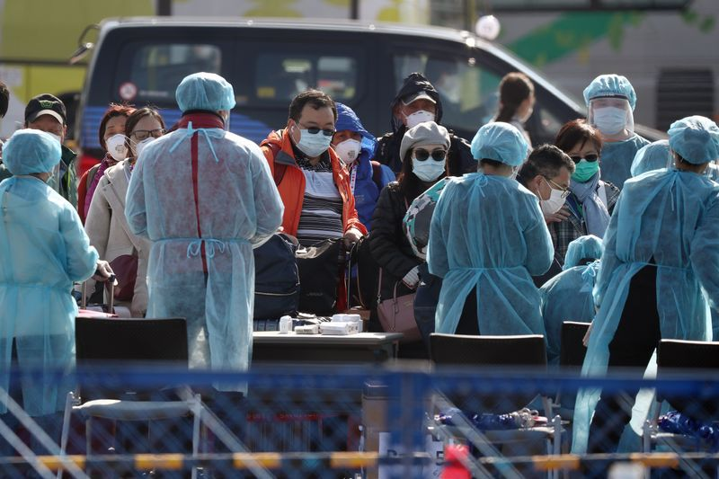 Trabajadores ayudan a los pasajeros cuando salen del crucero Diamond Princess, en la Terminal de Cruceros Daikoku Pier, en Yokohama, Japón. 21 de febrero de 2020. REUTERS/Athit Perawongmetha.
