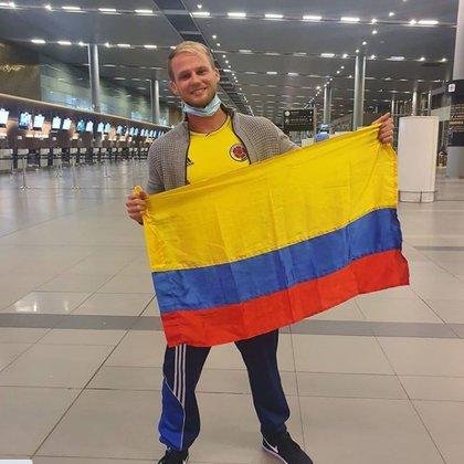 Dominic Fabián Wolf posa con la bandera de Colombia en el Aeropuerto El Dorado. (Captura de Instagram)