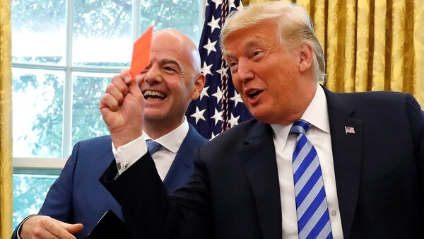 Infantino y Trump bromeando con las tajejtas (Reuters)