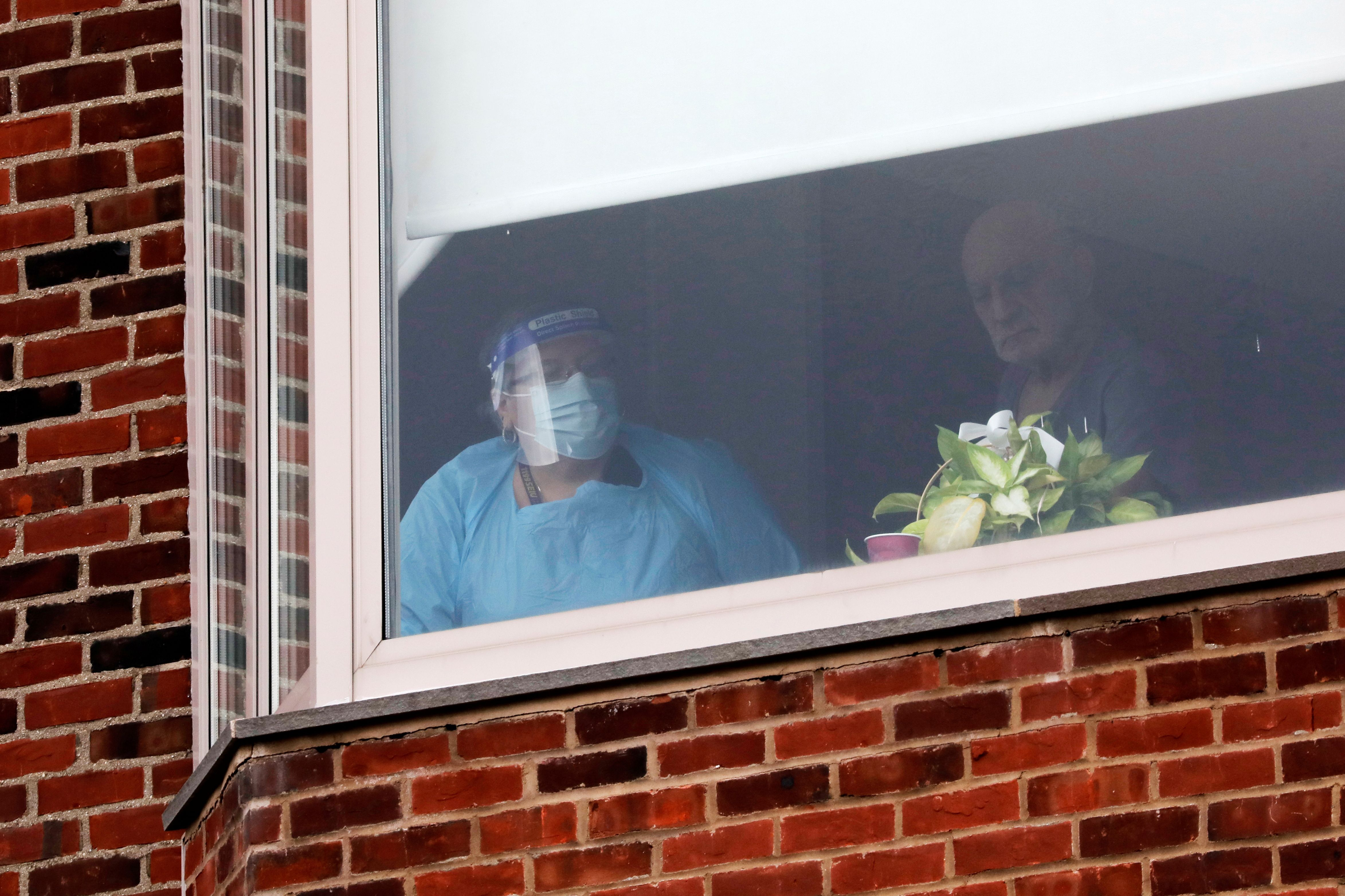 A nurse and a patient look out a hospital room window as union nurses with the New York State Nurses Association (NYSNA) walk the picket line below after walking out on strike at Montefiore New Rochelle Hospital in New Rochelle, New York, U.S., December 1, 2020. REUTERS/Mike Segar