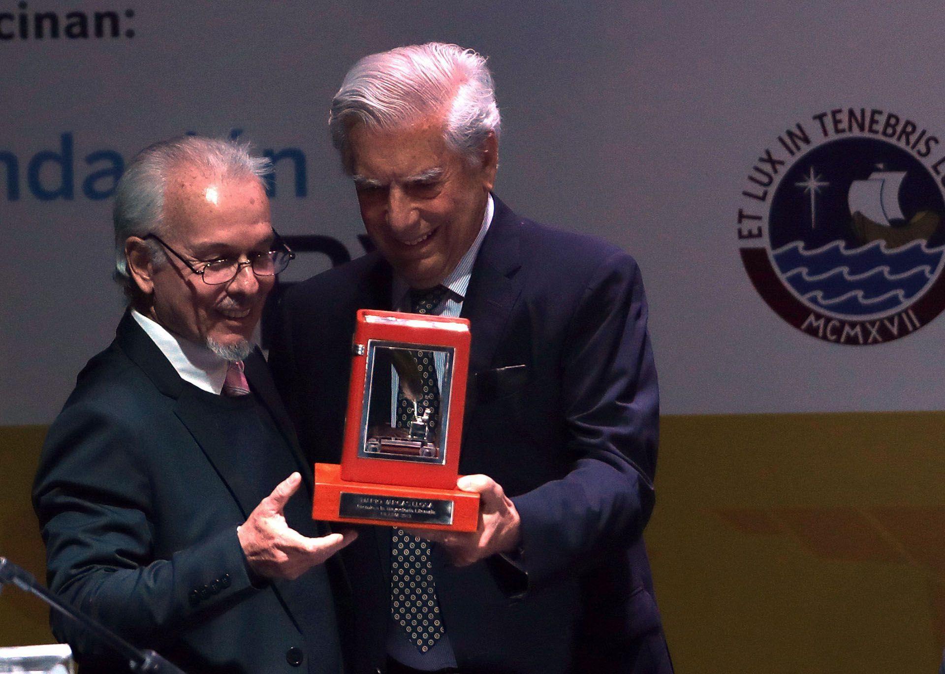 Mario Vargas Llosa recibe un premio de manos de José Carlos Alvariño, presidente de la Cámara Peruana del Libro(EFE/ Ernesto Arias)
