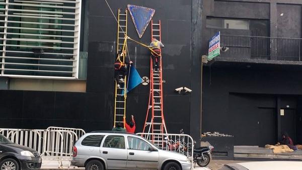 7 de junio, 12.50 horas: empleados quitan el cartel de Ideas del Sur del frente del edificio; debajo se ve el cartel del Grupo Indalo.