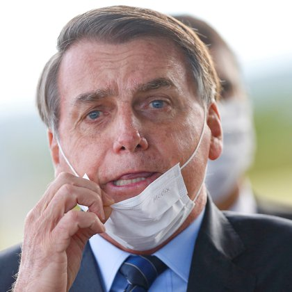 FILE PHOTO: Brazil's President Jair Bolsonaro adjusts his mask as he leaves Alvorada Palace, amid the coronavirus disease (COVID-19) outbreak in Brasilia, Brazil May 13, 2020. REUTERS/Adriano Machado     TPX IMAGES OF THE DAY/File Photo