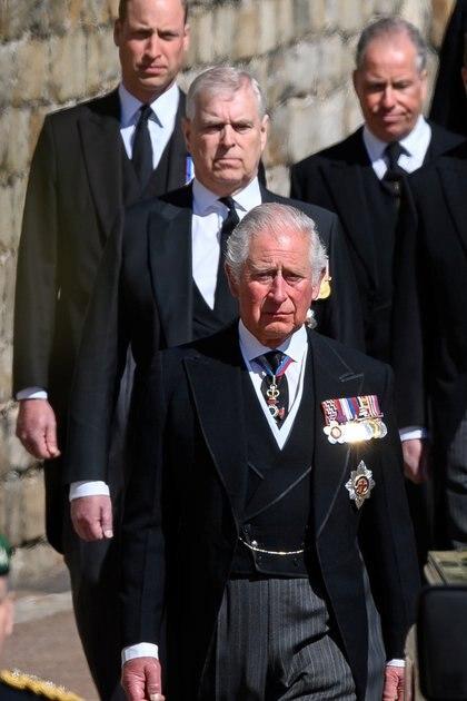 El príncipe Carlos seguido por su hermano, el príncipe Andrés, y el príncipe William