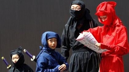 Una familia vestida de ninjas mira un mapa mientras buscan a los maniquíes ninja ocultos durante un festival ninja en Iga, a unos 450 km de Tokio (REUTERS/Kim Kyung-Hoon)
