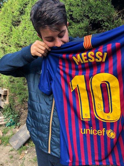 Con uno de sus trofeos: la camiseta del Barcelona firmada por Messi (Foto: @santialberione)