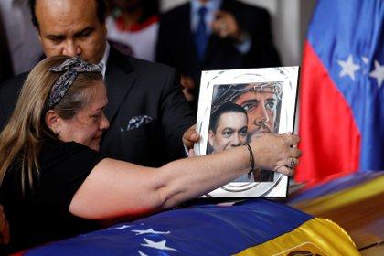 Luz Albán pone una foto sobre el ataúd de su hermano Fernando Alban durante una ceremonia en la Asamblea Nacional de Caracas (REUTERS/Marco Bello)