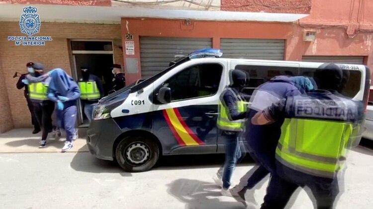 Hombres con la cabeza cubierta son llevados fuera de un edificio en Almería, España, el 21 de abril de 2020, en esta foto tomada de un video. Policía Nacional de España/Via REUTERS