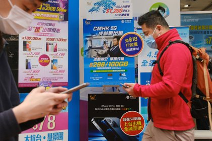 Pedestrian wearing protective masks walk past advertisements at a China Mobile Ltd. store in Hong Kong, China, on Monday, Jan. 4, 2021. China's state-owned telecommunications companies declined in Hong Kong after the New York Stock Exchange said it's delisting them to comply with a U.S. executive order that sanctioned companies identified as affiliated with the Chinese military.