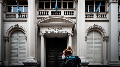 Una mujer camina frente a la sede del Banco Central, en el centro porteño. (EFE)