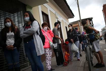 Personas usan mascarillas mientras hacen fila para ingresar a un supermercado durante el aislamiento obligatorio decretado por el gobierno colombiano, en Soacha (REUTERS/Luisa González)