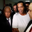 Former soccer star Ronaldinho is escorted by police to go before Judge Mirko Valinotti at the Justice Palace court in Asuncion, Paraguay, Friday, March 6, 2020. Ronaldinho has been detained by Paraguayan police for allegedly entering the country with a falsified passport. (AP Photo/Jorge Saenz)